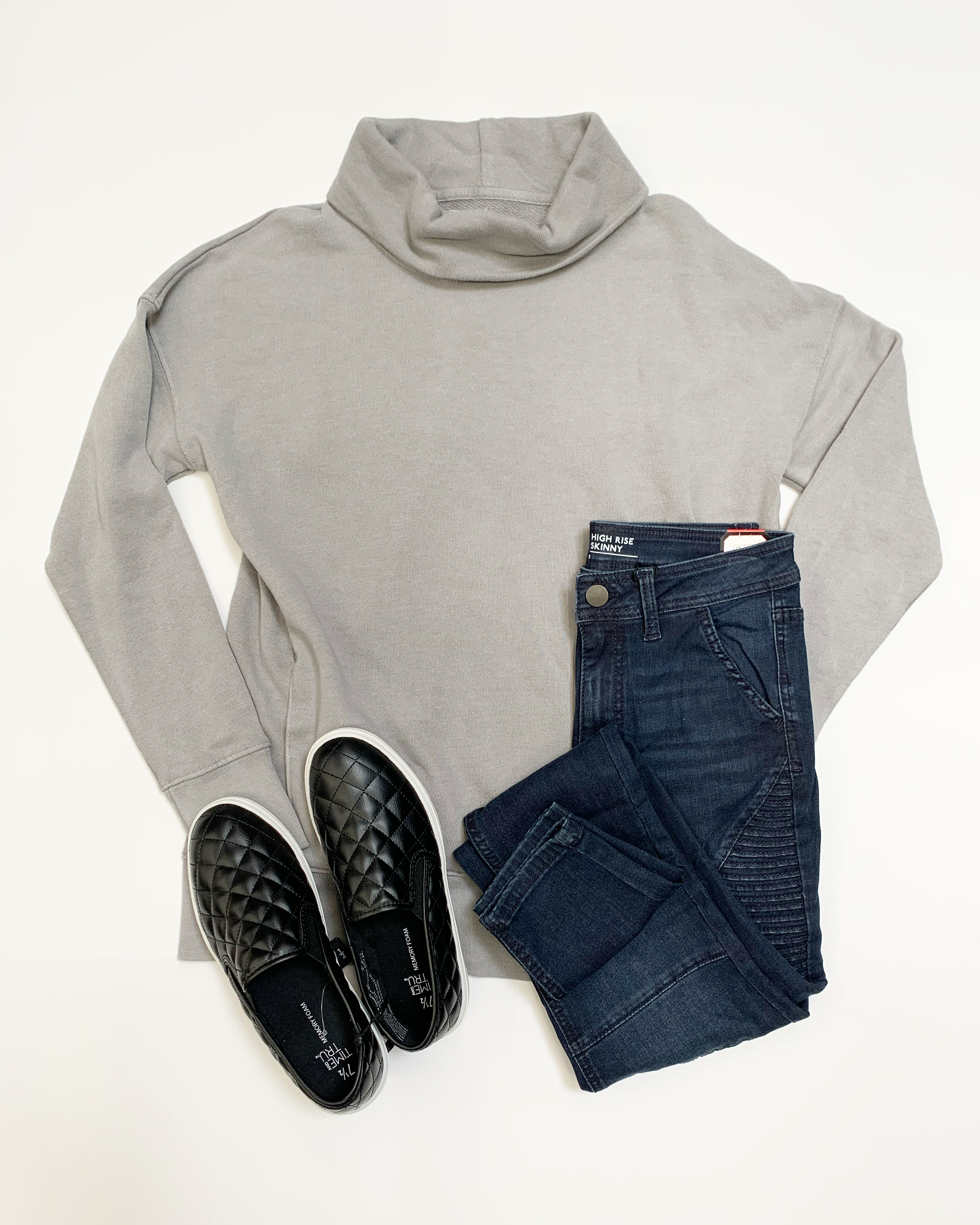 flat lay clothing photo with cowl neck sweatshirt and moto jeans