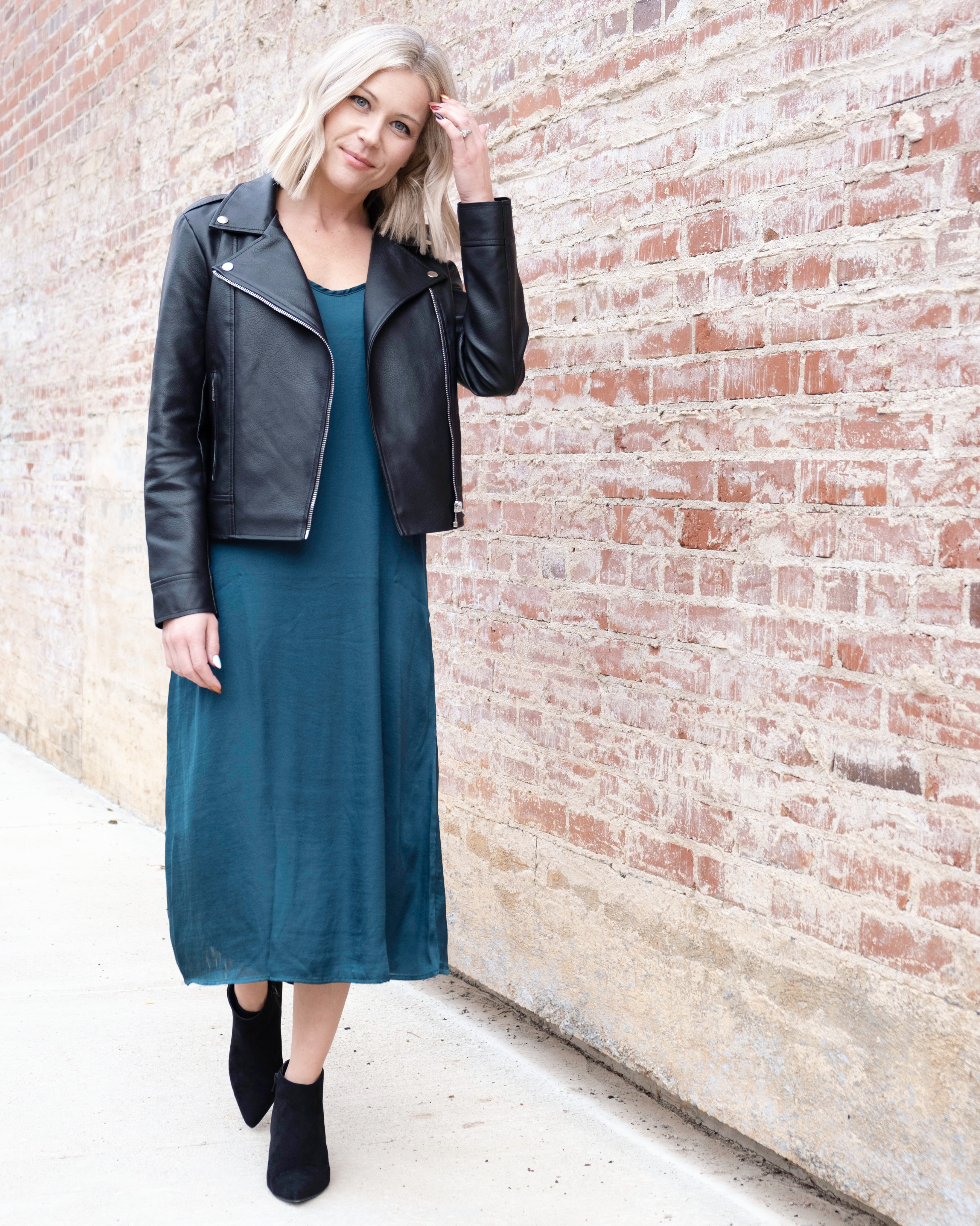 woman wearing an emerald green slip dress with faux leather moto jacket