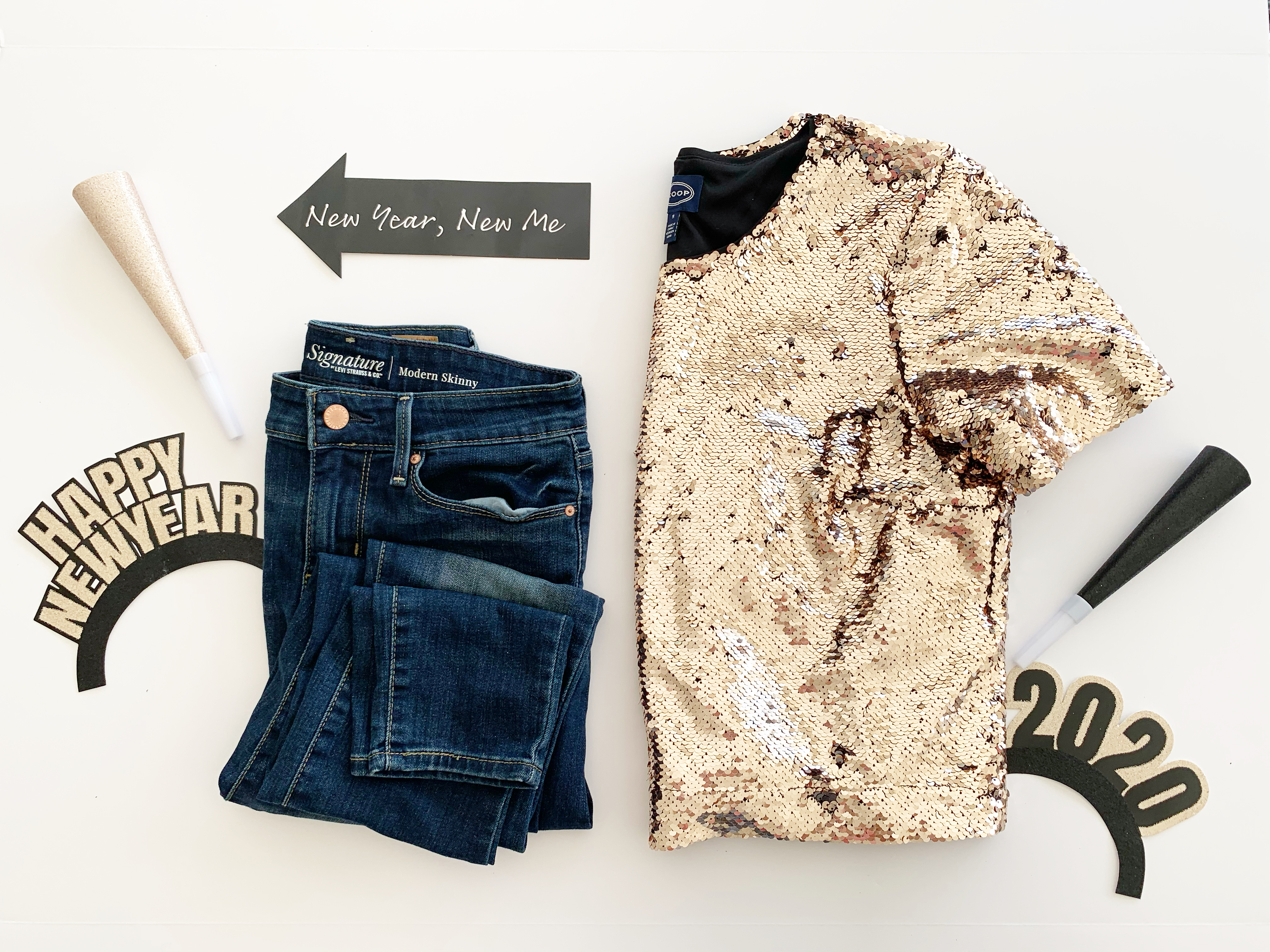 flat lay style photo with sequin top and jeans with NYE decor
