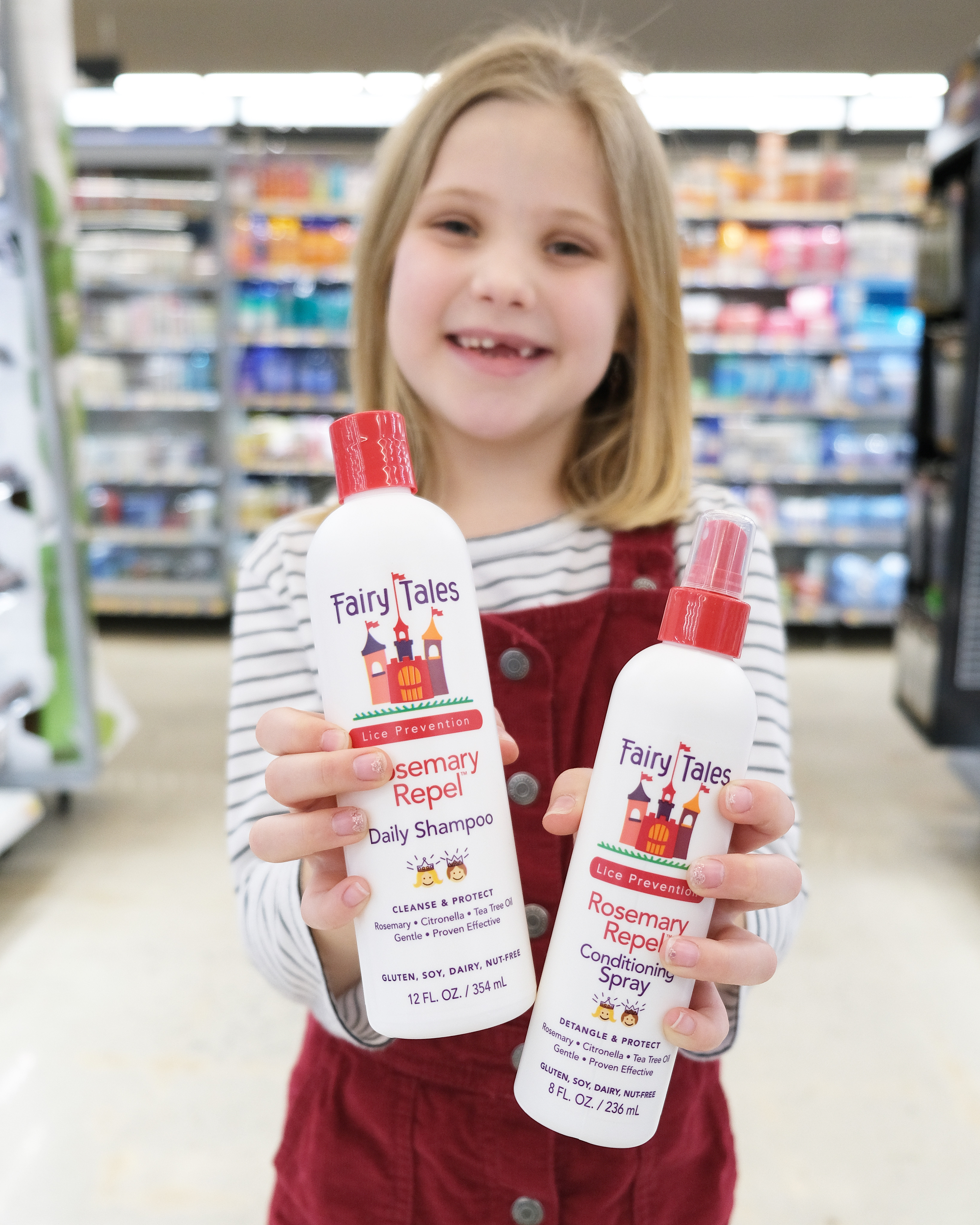 little girl holding shampoo and conditioning spray in Walmart