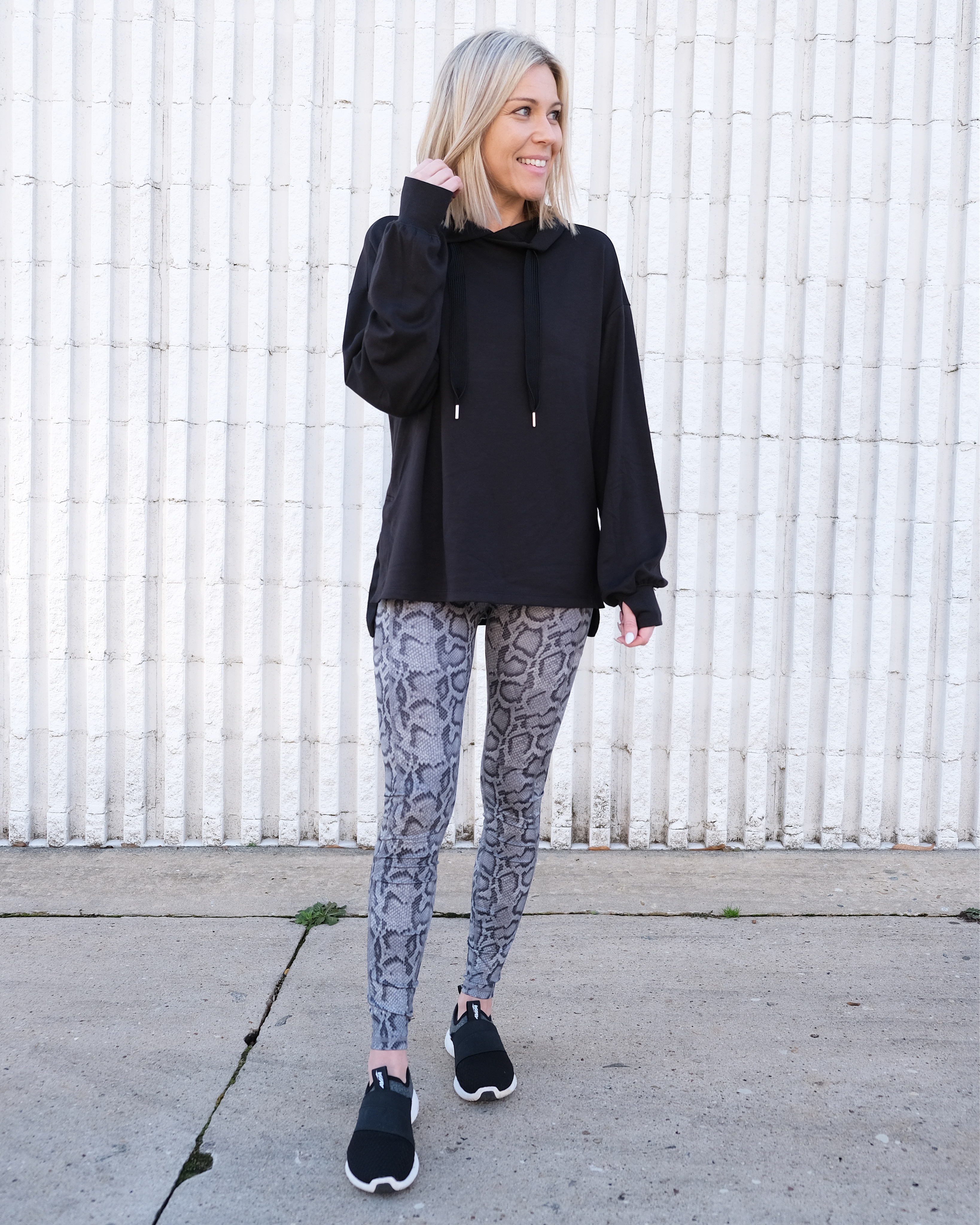 woman wearing black tunic with snake print leggings and sneakers